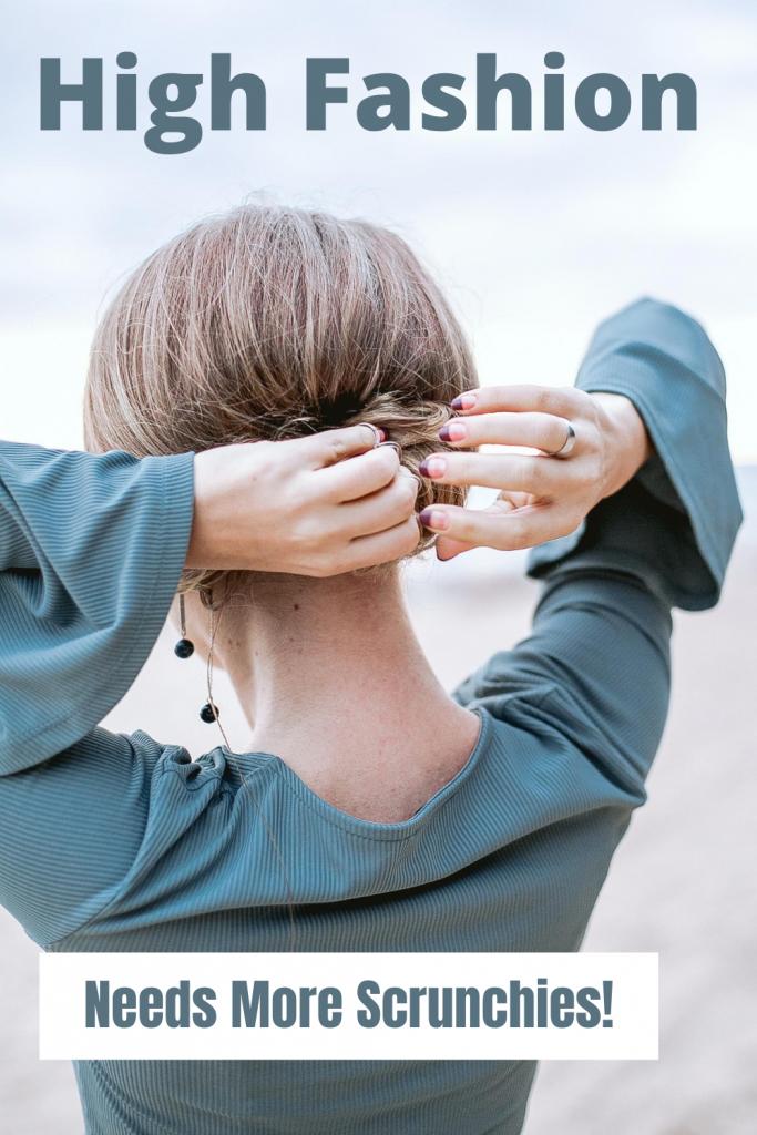 woman in dress putting hair in bun